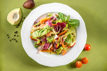 salad with avocado and cherry tomatoes on green background, top