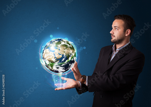 Businessman holding glowing earth globe