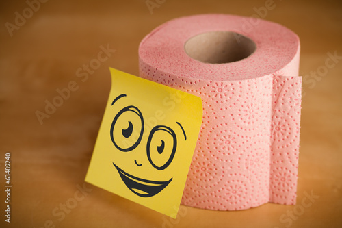 Post-it note with smiley face sticked on toilet paper