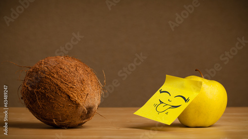 Apple with post-it note sticking out tongue to coconut