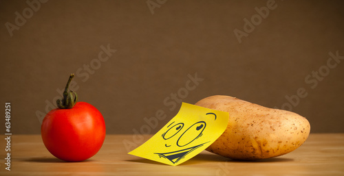 Potato with post-it note looking curiously at tomato