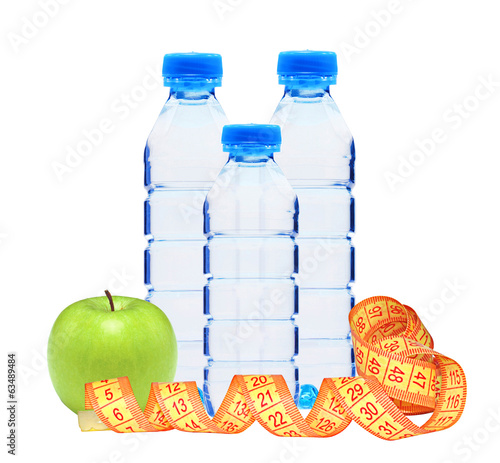 Blue bottles with water, measure tape and green apple isolated o
