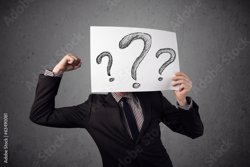 Businessman holding a paper with question marks in front of his