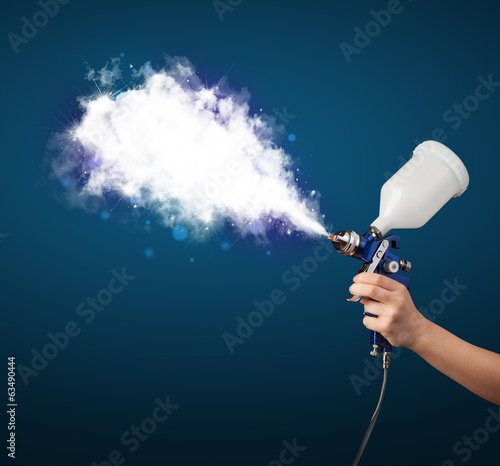 Painter with airbrush gun and white magical smoke