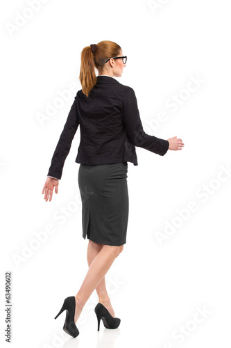 Walking woman, rear angle view.