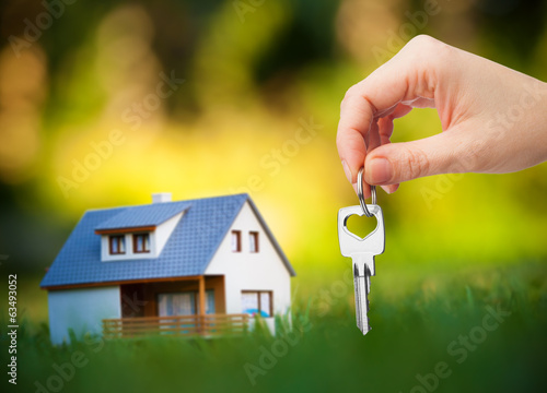 canvas print picture hand holding key against house background