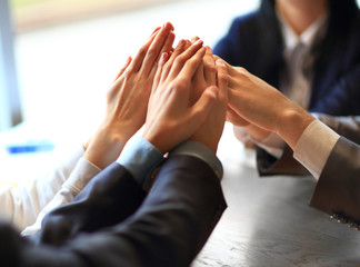 Image of business people hands on top of each