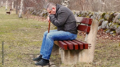 Man with walking stick on bench in the park