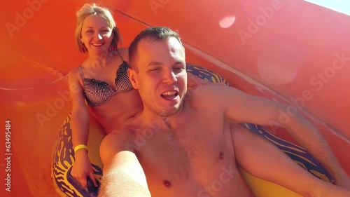 Man and woman sliding down the waterslide in a waterpark