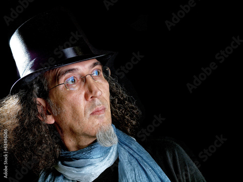 Man with long hair, goatee beard and top hat on black background