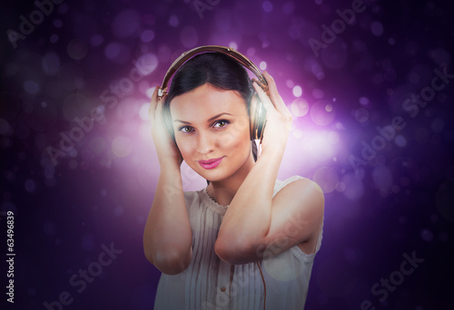 Beautiful woman listening music on a background of lights