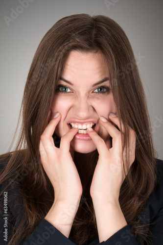 Frightened and stressed young business woman biting her fingers