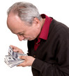 Old man looking at dollar bills
