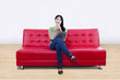 Asian female thinking on red sofa with laptop at home
