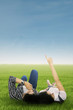 Couple lying on grass pointing at sky
