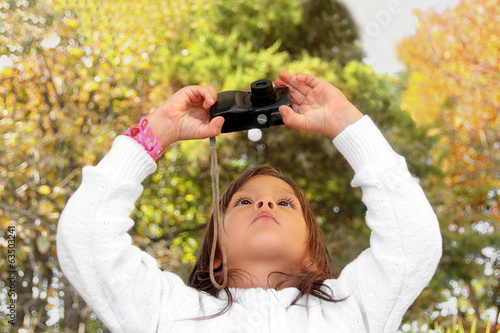 Little girl taking a picture to the digital camera outdoors