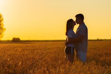Young couple kissing in the field of wheat