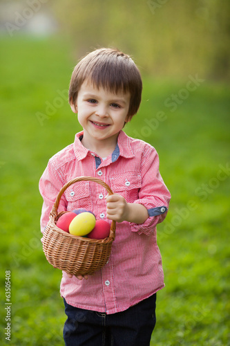 Little cute boy, holding basket with colorful easter eggs