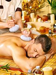Man getting herbal ball massage treatments .