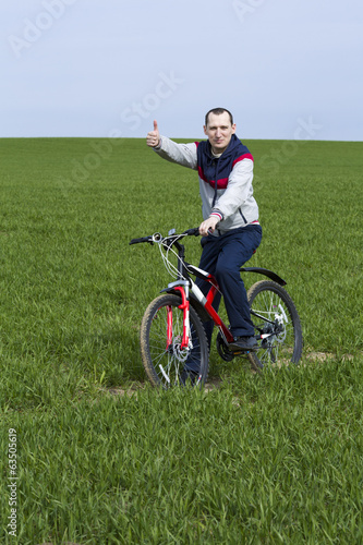 Man with bike on green field