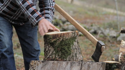 Man with an ax chops wood for heating