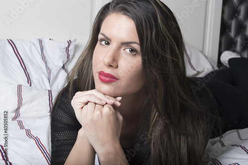 Portrait of a beautiful woman lying in a bed