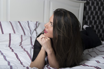 Portrait of a beautiful woman lying on a bed (profile)