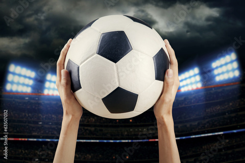 Hands holding soccer ball at stadium