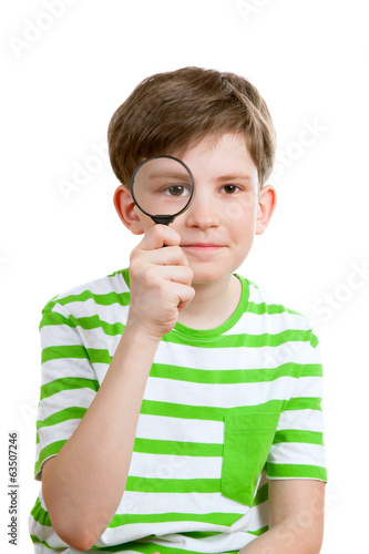 The boy holds loupe opposite his eye