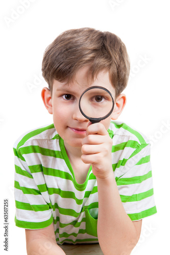 Small boy with magnifier on white background
