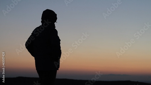 Silhouetted man standing in sunset on mountain