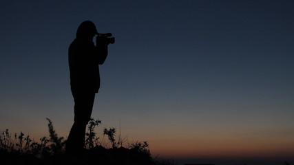 Silhouetted man standing in sunset on mountain with camcorder