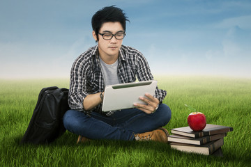 Male student using digital tablet outdoors