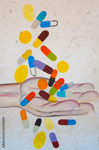 Male hand catching falling pills