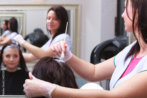 Woman dying hair in hairdressing beauty salon. By hairstylist. - 63509270