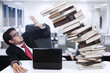 Stress businessman and falling books at office
