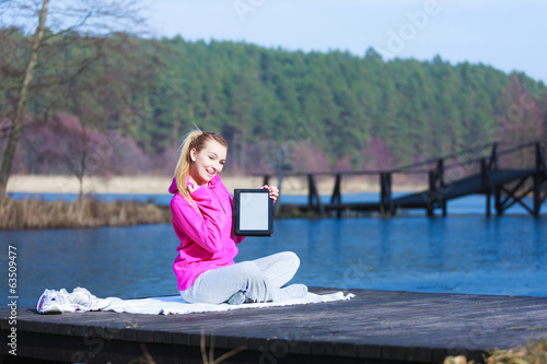 Woman teenage girl in tracksuit showing tablet on pier outdoor