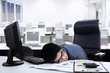 Tired businessman sleeping on the desk