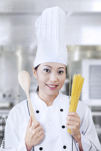 Young chef holding pasta