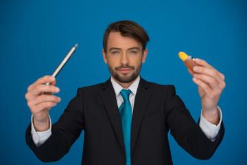 businessman holding e-cigarette and e-liquid on blue
