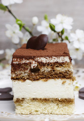 Tiramisu cake on white plate. Blossom apple