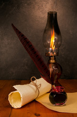 Feather pen with ink, scroll and kerosene lamp