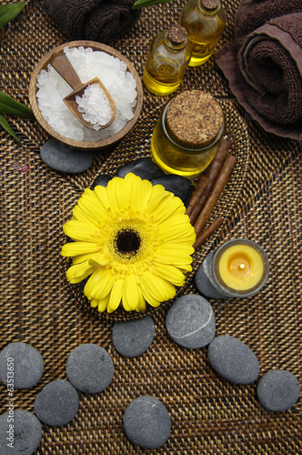 salt and daisy with stones and candle on burlap texture