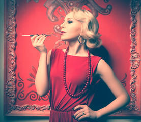 Sensual woman in red dress smoking