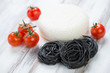 Black raw tagliatelle with cheese and tomatoes, horizontal shot