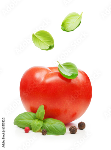 Red tomato and basil leaves spice falling down