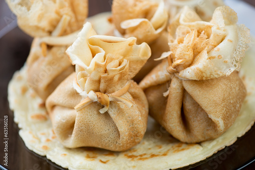 Close-up of freshly made stuffed crepes, horizontal shot