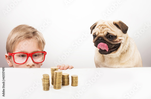 Funny boy and his dog staring at piles of coins