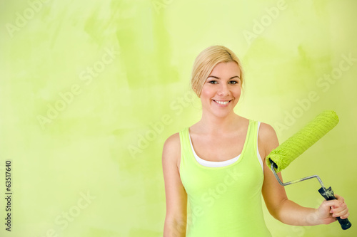 Portrait of smiling woman with paint roller