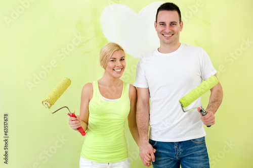 Portrait of love couple with paint rollers